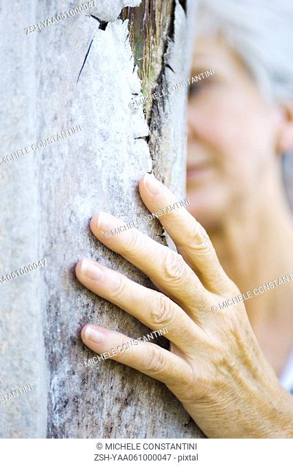 Senior woman touching tree trunk, cropped view, close-up