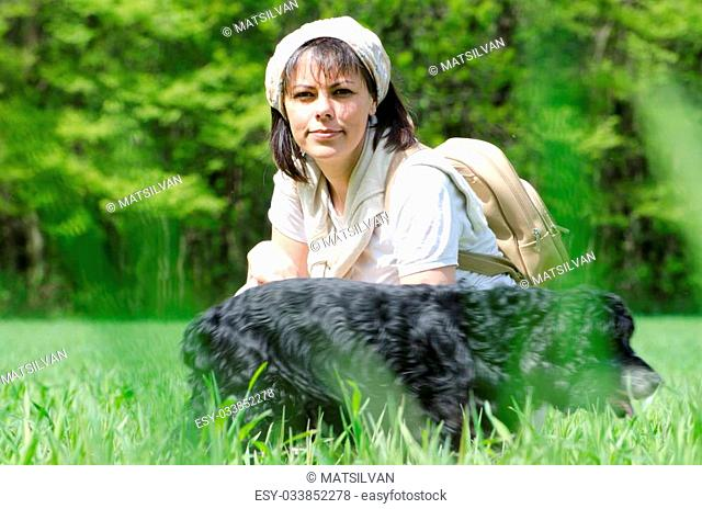 Travel woman with scarf and backpack on the green field with grass and trees and a dog