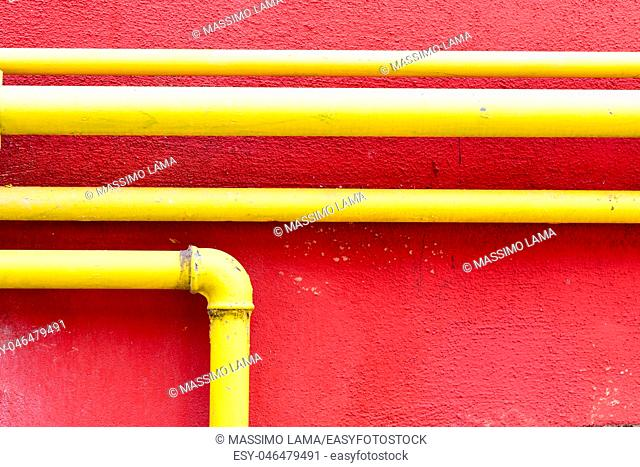 yellow gas pipe on a pompeian red wall