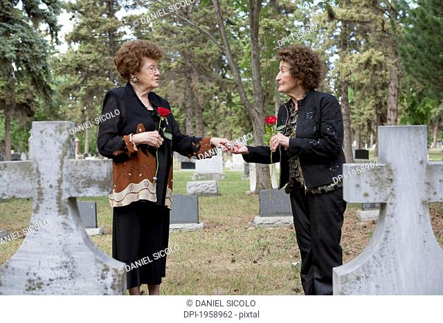 Two Women Holding Single Red Roses At A Grave In A Cemetery; Edmonton, Alberta, Canada