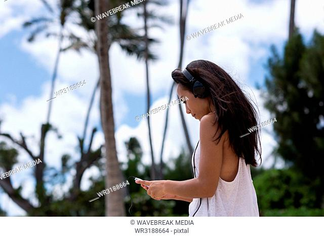 Woman using mobile phone in the beach