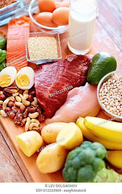 balanced diet, cooking, culinary and food concept - close up of vegetables, fruits and meat on wooden table