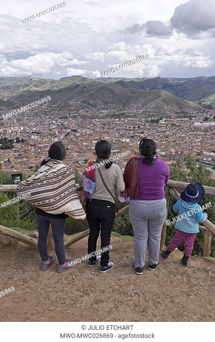 Native Quechua women and children taking the views of Cusco from the citadel of Sacsahuayman, a native Inca complex surrounded by walls that were made by...
