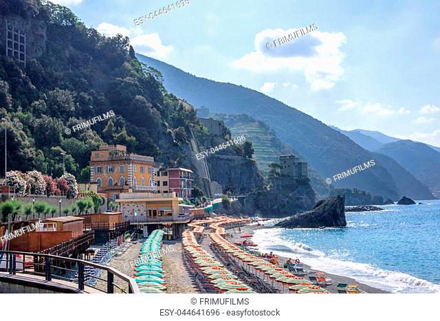 Beautiful daylight view to blue sea and green mountains in fog. Monterosso al Mare, Italy. Cinque Terre