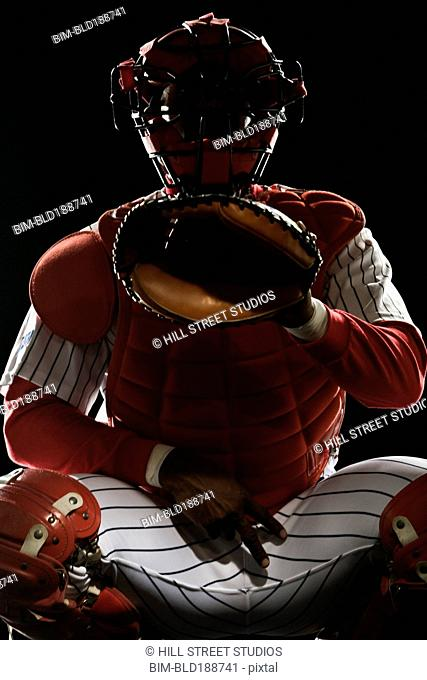 African baseball catcher gesturing during game
