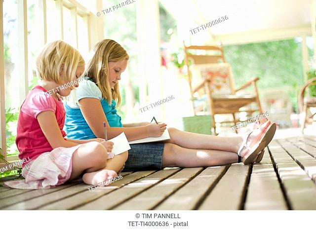 Two girls writing letters