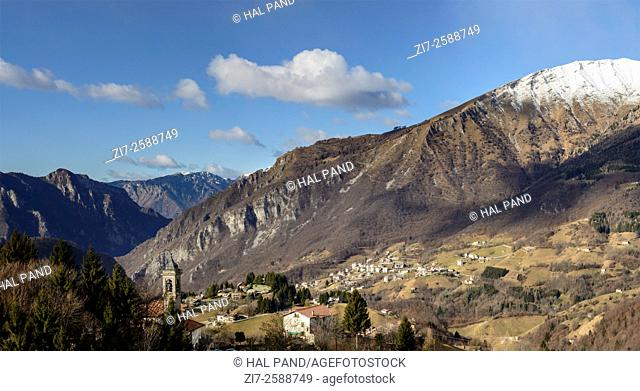 landscape with mountain village and the rocky slope of Menna peak in Bergamo mountains in a winter with little snow, shot in bright winter light