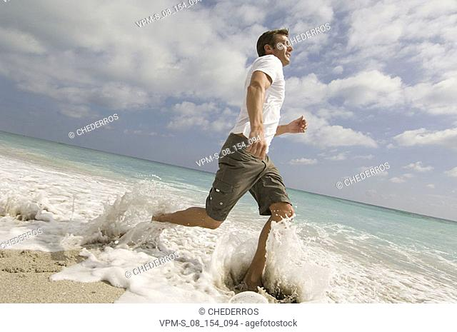 Low angle view of a mid adult man running on the beach