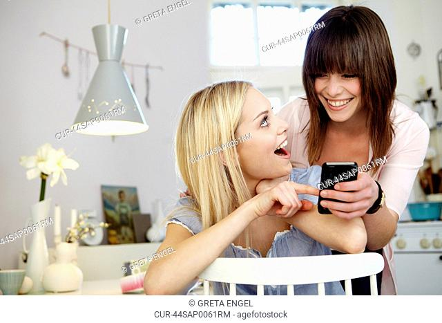 Women using cell phone together