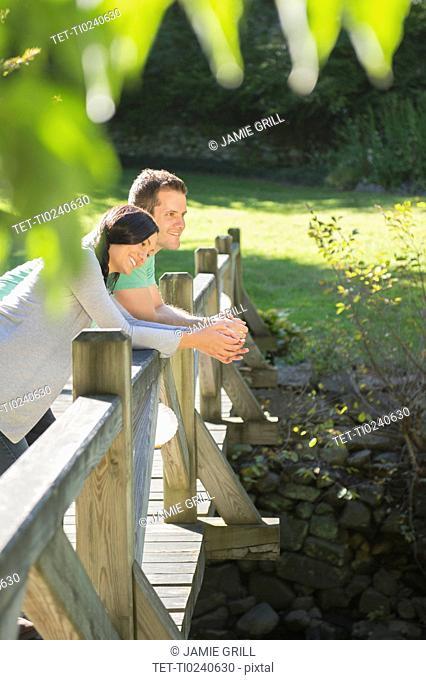 Couple standing on wooden bridge