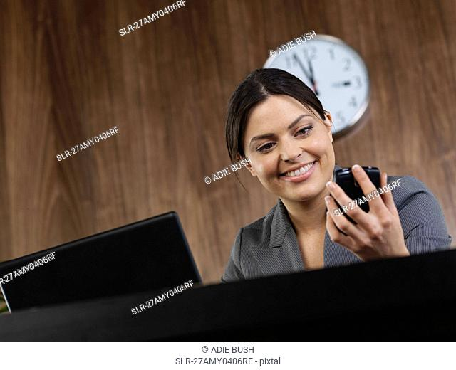 Business woman at desk with phone
