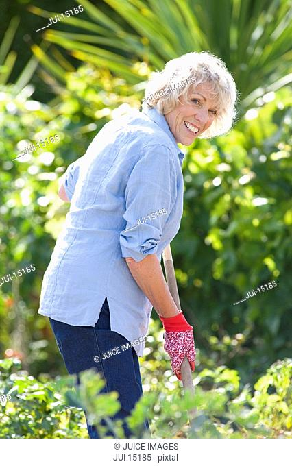 Senior woman gardening, portrait