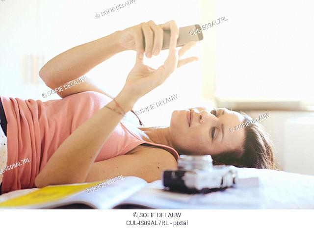 Mid adult woman lying on bed reading messages on smartphone