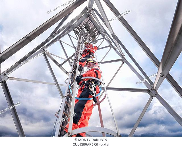 Tower workers climbing radio tower on offshore windfarm, low angle view