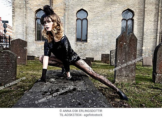 Lone female figure wearing black lace standing on a grave