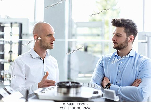 Two men discussing product in company