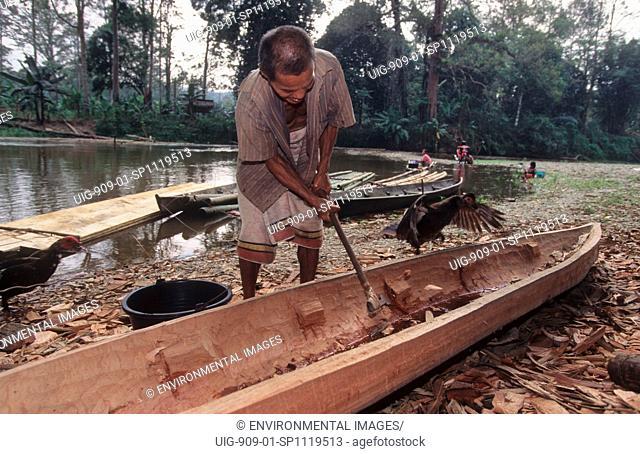 MAKING A DUG-OUT CANOE, SUMATRA, INDONESIA.