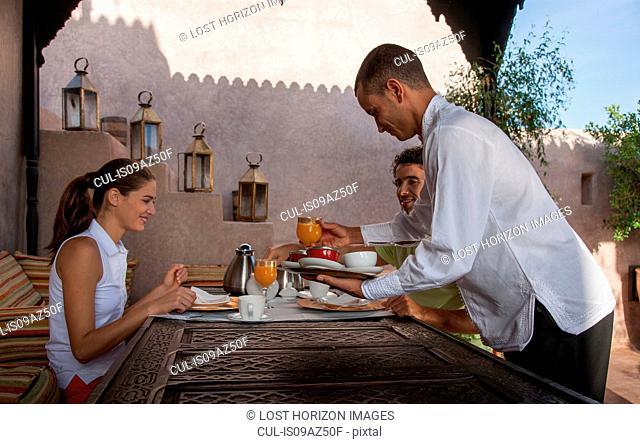 Waiter serving young couple breakfast, Marrakesh, Morocco