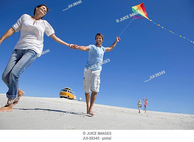 Happy family with kite running on sunny beach with van in background
