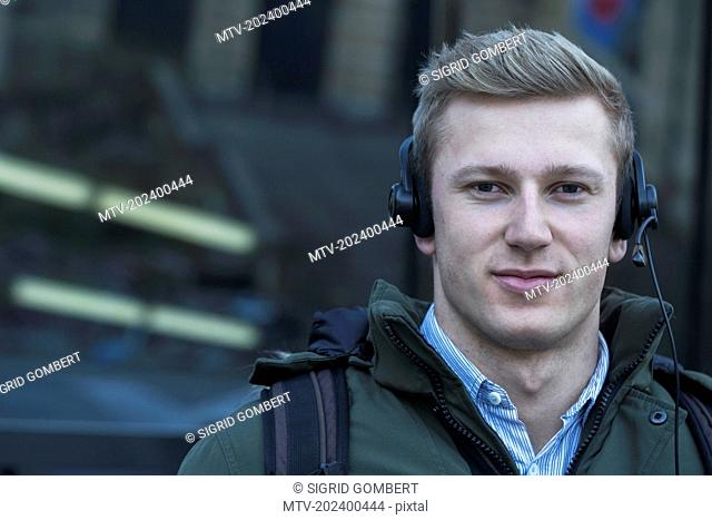 Close-up of young man listening to music with headset, Freiburg im Breisgau, Baden-Württemberg, Germany