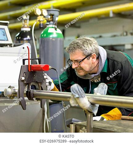 Industrial operator setting computer controlled process of orbital welding machine in stainless steel pipes manufacturing workshop