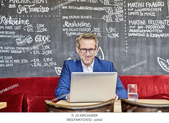 Portrait of confident mature businessman in cafe using laptop