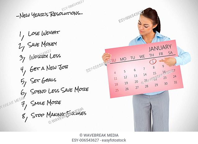 Composite image of young businesswoman looking at the calendar she is presenting