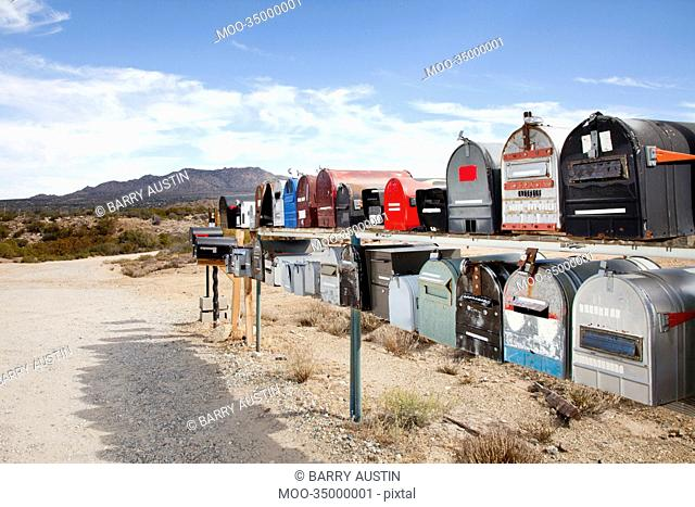 Rows of mailboxes in desert with mountains in background