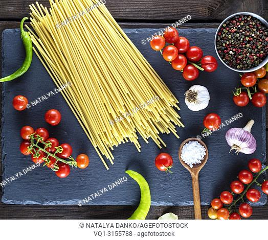 pasta spaghetti on black background, red cherry tomatoes and garlic for sauce, top view