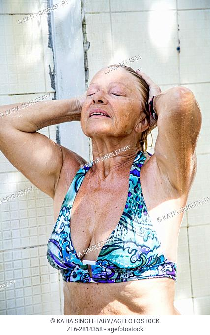 Older retired senior caucasian woman showering at the beach in a blue bathing suit
