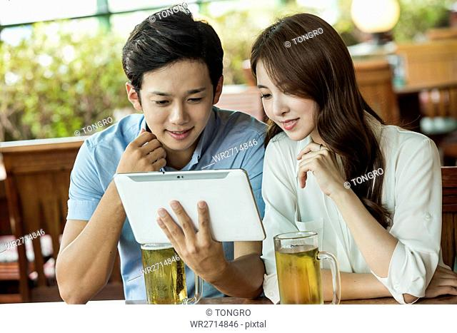 Young smiling business people sharing tablet
