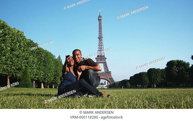 couple taking their own photo in front of the Eiffel tower