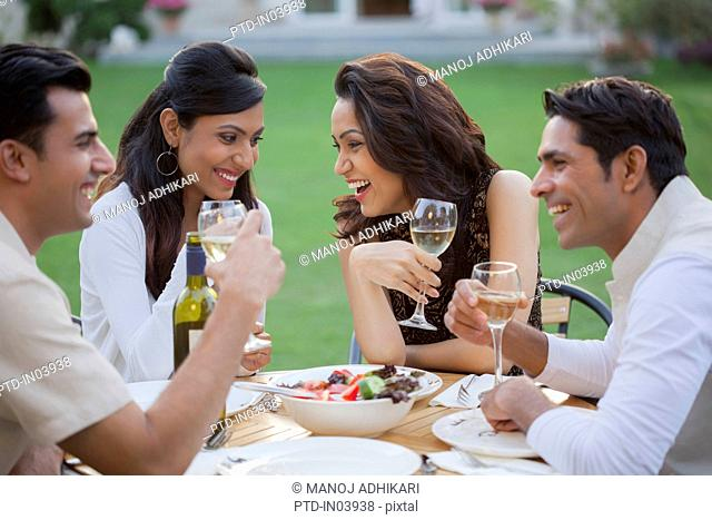 India, Friends drinking wine at table on backyard