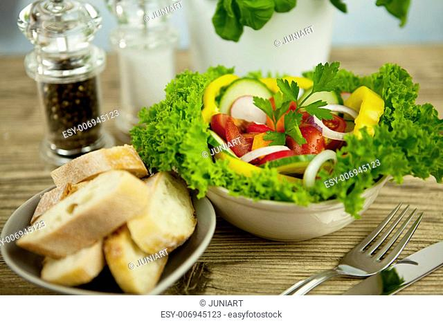 fresh tasty healthy mixed salad and bread on wooden table