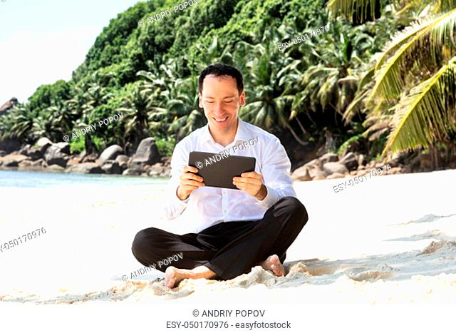 Smiling Young Man Sitting On The Sandy Beach With His Crossed Legs Using Digital Tablet