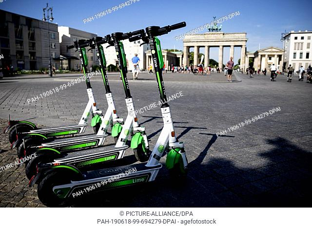18 June 2019, Berlin: E- pedal scooters of the US-American company Lime stand in front of the Brandenburg Gate for rental
