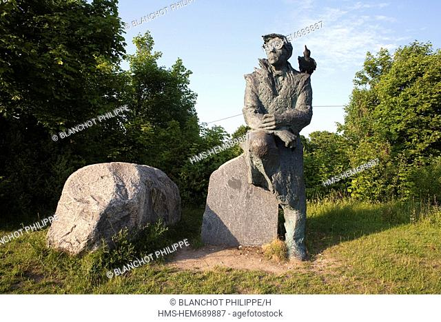 Estonia Baltic States, Saare Region, Muhu Island, sculpture of Juhan Smuul, writer and poet, sitting facing the sea, with a raven on his shoulder