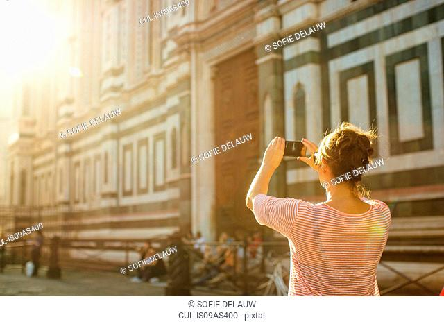 Rear view of mid adult woman using smartphone to take photograph, Duomo Cathedral, Florence, Italy