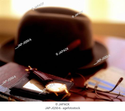 Hat, boarding pass and watch on table