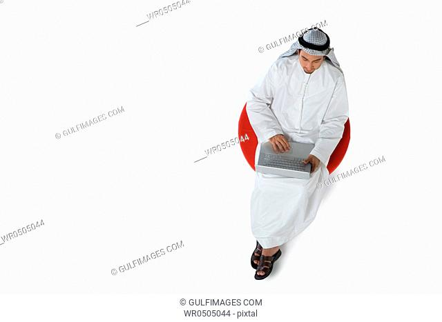 Young man sitting on chair, using laptop, top view