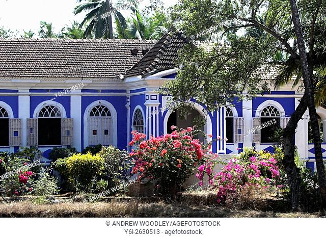 Attractive blue and white single storey country house Casa Robello with shutters and tropical flowers Anjuna Goa India