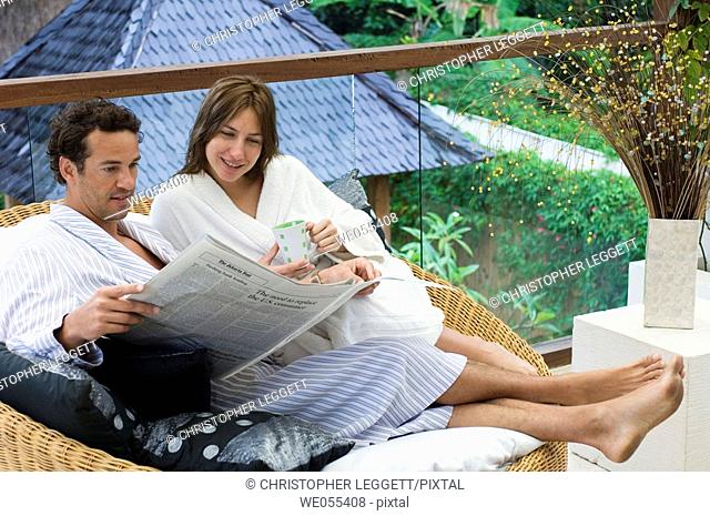 young couple in bathrobe sitting and reading newspaper on sofa