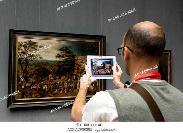 Visitor with tablet camera at Gemèldegalerie art museum in Berlin, Germany