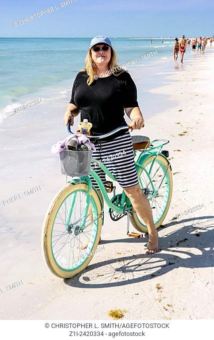 Adult female with her beach-cruiser bicicyle on Siesta Key beach in Sarasota Florida