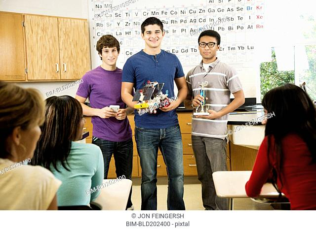 High school students holding solar powered machine and trophy