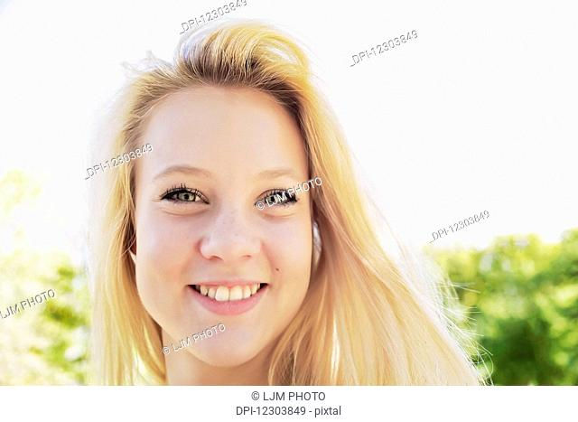 Portrait of a beautiful young woman with long blond hair in a city park; Edmonton, Alberta, Canada