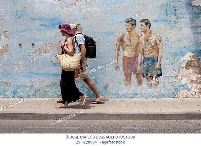 Pair of swimmers watch tourist couple, Roses, Catalonia, Spain