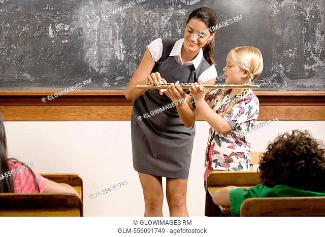 Teacher helping a schoolgirl playing a flute in a classroom