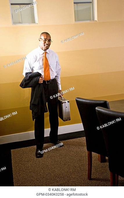 Smiling businessman standing in office holding briefcase