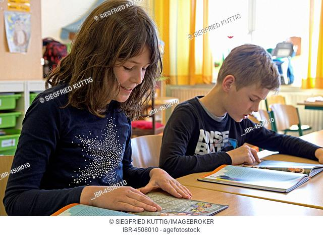 Students, children reading a book, German lessons, primary school, Lower Saxony, Germany